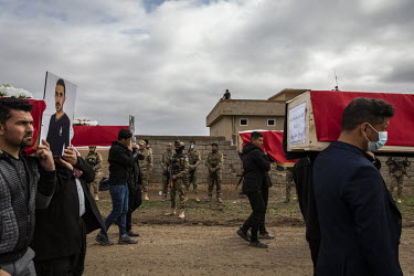 Soldiers look on as pallbearers walk past carrying coffins during a funeral procession for 103 Yazidis killed by ISIS in the village of Kocho in 2014. Having been exhumed from the mass graves where th...