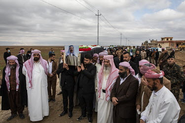 A photograph of a Yazidi man displayed on one of the coffins being carried by pallbearers during a funeral procession for 103 Yazidis murdered by ISIS in the village of Kocho in 2014. Having been exhu...