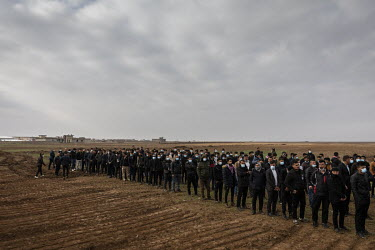 Pallbearers line up in preparation to carry the remains of 103 Yazidi victims who were killed by ISIS in the village of Kocho in 2014. Having been exhumed from the mass graves where they were dumped b...