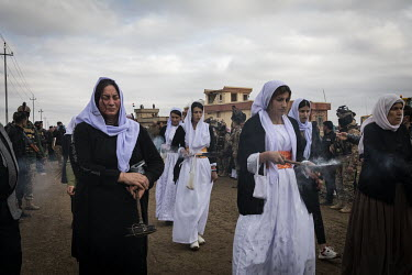 Yazidi women burn incense during a funeral procession for 103 Yazidis killed by ISIS in the village of Kocho in 2014. Having been exhumed from the mass graves where they were dumped by ISIS, the victi...