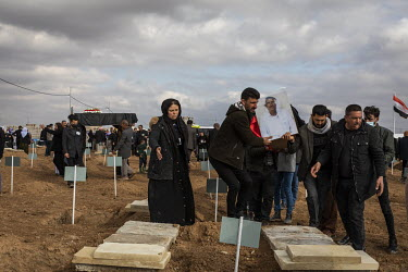 Yazidi family members from the village of Kocho bury the remains of their loved ones in front of the school building where, in 2014, ISIS rounded up the boys, men and elderly women of the village befo...