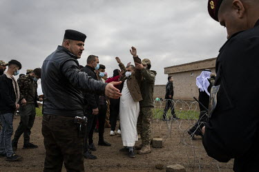 A man is searched by soldiers during a funeral ceremony for 103 victims of ISIS terror where security was extremely tight. In 2014, ISIS rounded up the boys, men and elderly women of Kocho village bef...