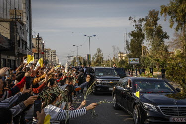 Pope Francis waves from his motorcade to the crowds of people who have come to see his visit to Erbil.