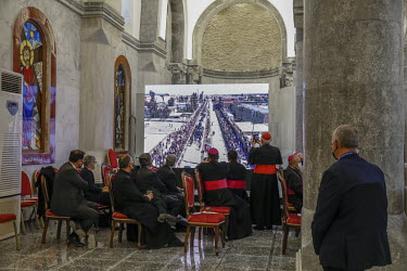 Clergy in the Church of Immaculate Conception watch a television broadcast of Pope Francis' motorcade as it passes along the crowded streets of the mainly Christian town of Qaraqosh towards the church...