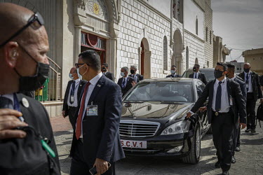 Security personnel walk with Pope Francis's motorcade after he left the Church of Immaculate Conception, in the mainly Christian town of Qaraqosh, where he held mass.