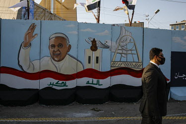 A security guard walks past a mural of of Pope Francis painted on blast walls in front of the Our Lady of Salvation church in Baghdad, shortly before the Pope was due to arrive.