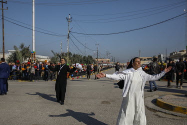 A nun and a priest enage with the crowds of people lining the streets to greet Pope Francis on his visit to the mainly Christian town of Qaraqosh.