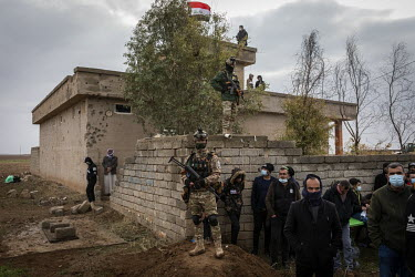 Security personnel and residents look on as the funerary procession for 103 Yazidi victims of ISIS passes them by. Having been exhumed from the mass graves where they were dumped by ISIS, the victim's...