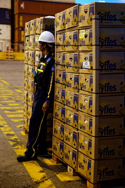 A worker stands beside a stack of Fair Trade bananas, boxed and ready to be shipped from Santa Marta's port.