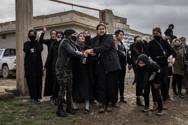 A group of distraught female relatives comfort each other as the funerary procession for 103 Yazidis killed by ISIS passes them by. Having been exhumed from the mass graves where they were dumped, aft...