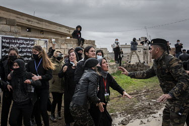A soldier tries to calm a group of distraught women as the funerary procession for 103 Yazidi victims of ISIS terror passes them by. Having been exhumed from the mass graves, where they were dumped fo...