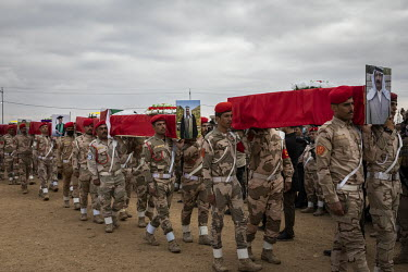Iraqi soldiers act as pallbearers, carrying coffins during a funeral procession for 103 Yazidis killed by ISIS in the village of Kocho in 2014. Having been exhumed from the mass graves where they were...