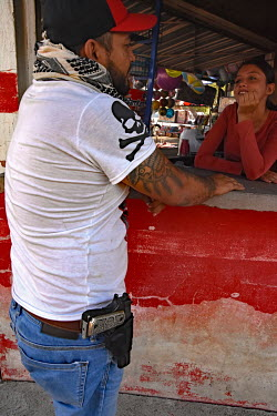 A member of 'Los Viagras', an armed vigilante group that call themselves 'grupos de autodefensas' (self-defence militias), talking to a woman working in a stall while on patrol. The controversial vigi...