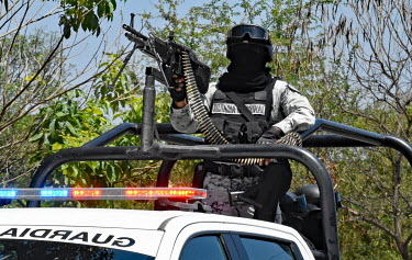 A heavily armed Guardia Nacional mobile patrol drives through Buenavista.
