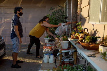 Gloria Itzel Montiel accepts a bag from her grandmother after delivering food to her with her brother, Israel, while assisting families in need during the pandemic in Santa Ana. The bag from her grand...