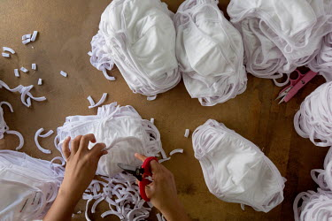 An employee works on masks at a garment factory owned by the sister of Gisel Villagomez, 33, who works there as a project and contracting manager.   Gisel is a Deferred Action for Childhood Arrivals (...