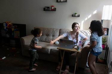 Marivic Danino Grijalva, 24, with her children while home working providing tech support online. She juggles work and homeschool on the days she is not working at the MonteCedro Retirement Community i...