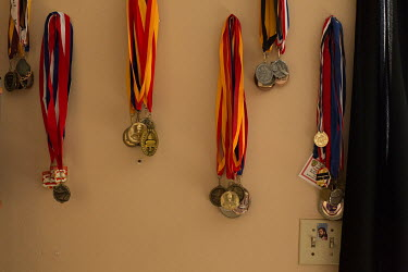 Academic medals hang on the wall in Ana Zamora's home. Ana is a Deferred Action for Childhood Arrivals (DACA) recipient and an essential worker.   Ana Zamora, 21, came to the United States from Tiju...