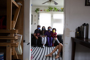 Alma with her family at her house in Los Angeles. Alma is a Health Worker linkage to Care Coordinator in LA county. She has worked throughout the pandemic providing health services to the community. A...