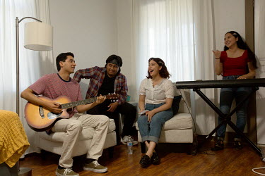 Ana Zamora (white top) jams with her band at the pastor's house where they practice and records songs to be uploaded to the internet for members of the Spanish-American Seventh Day Adventist Church. A...