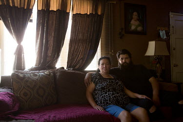Alejandro Ortega Picon, 27, sits on the couch with his mother, Maria Luisa, 54, beneath a photo of his mother at her house.   A Deferred Action for Childhood Arrivals (DACA) recipient who works at the...
