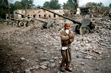 A boy passes the ruins of a former Taliban barracks bombed by the American air force.