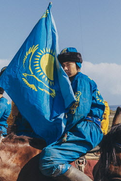 A Kazakh Kok-Boru player carries his nation's flag ahead of the team's 3rd place play-off match with Russia.
