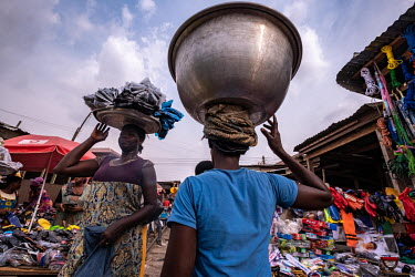 Traders, carrying their wares in basins on their heads, walk through Kejetia market (Kumasi Central Market). The market is thought to be amongst the largest in Africa, with over 10,000 individual stor...