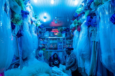 A woman examines wedding dresses for sale in a stall in Kejetia market (Kumasi Central Market). The market is thought to amongst Africa's largest, with over 10,000 individual stores.