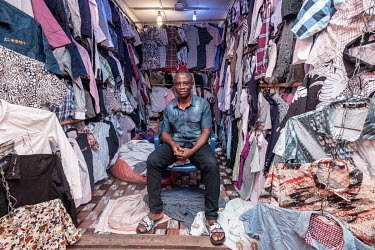 Second hand clothes salesman Oppong Antwi (50) in his stall in Kejetia market (Kumasi Central Market). Antwi says the business can be a gamble. Each 55kg bale of reject clothes contains around 400 shi...