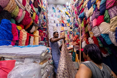 A fabric vendor serves a customer in his stall in Kejetia market (Kumasi Central Market).