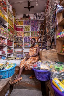 Agyekum Abrokwah Joyce (26) sits in her stall in Kejetia market (Kumasi Central Market) from where she sells a range of plastic items imported from China.