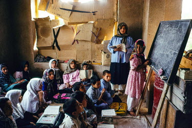 Boys and girls study in a clandestine school where the windows were covered up to hide their activity. The Taliban had closed down the girls' schools in Herat 18 months earlier, but the community set...