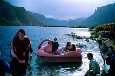 Families relax in a novelty paddle boat on Band-e Amir lake.