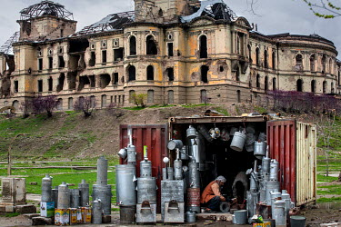 A tinsmith carrying on his father's trade, working in a shipping container set up as a store in front of the ruins of Darul Aman Palace.