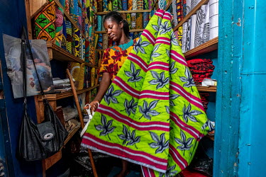 Fabric seller Rita Owusu (35) in her stall in Kejetia market (Kumasi Central Market) where she sells both locally manufactured and imported printed wax fabrics (Dutch wax prints) which remain extremel...