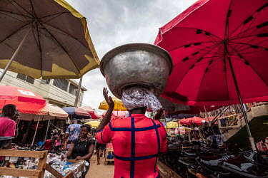 A trader walks through Kejetia market (Kumasi Central Market) carrying a metal basin on her head.
