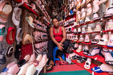 Florzy Anderson sells shoes in a wedge-shaped stall at a busy junction in the middle of Kejetia market (Kumasi Central Market), one of the largest on the continent. The shoes are mostly imported from...
