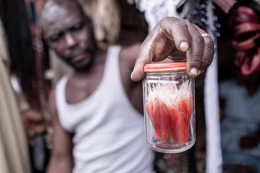 A traditional medicine vendor displays a jar of African grey parrot feathers in Kejetia market (Kumasi Central Market). African grey parrots are frequently poached from the wild both for use in tradit...