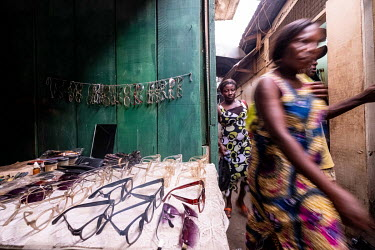Shoppers walk past a stall selling second hand gloasses in Kejetia market (Kumasi Central Market).