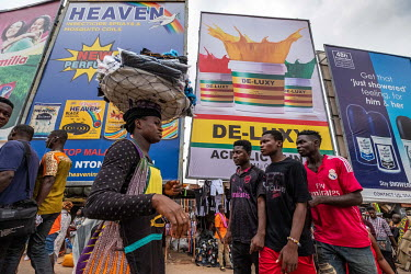Shopers and traders walk past advertising billboards in Kejetia market (Kumasi Central Market).