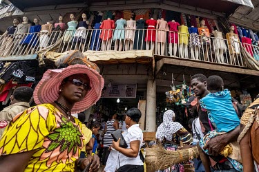 Shoppers walk past a clothes store in Kejetia market (Kumasi Central Market).