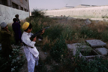 A boy shoots with an AK47 at Pul-e-Charkhi prison, notorious for the cruel treatment of detainees and prison riots.