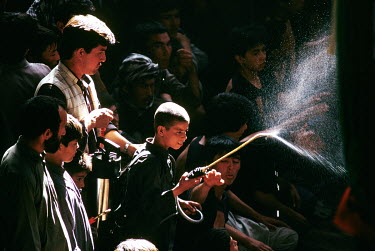 A boy sprays water to cool participants as Shia Muslims commemorate Ashura inside a mosque in the Chindawol district.