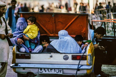 Men sit in the seats of a taxi while women and children are transported in its open boot.