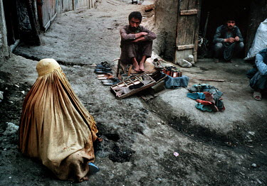 A widow wearing a burkha begging on a street beside a cobbler and sandal vendor.