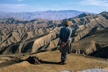 Ahmad Shah Massoud stands on high ground above the city of Taloqan. The night before the Taliban had violated a ceasefire and attempted to take the city. Massoud is pacing back and forth on the roof o...