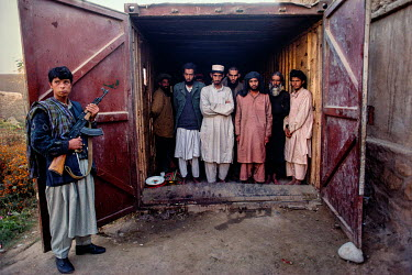 A Northern Alliance fighter guards Taliban prisoners held in a shipping container.