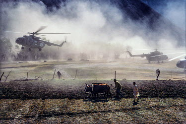 Helicopters from Ahmad Shah Massoud's forces take off from open ground beside farmers plouging a field.