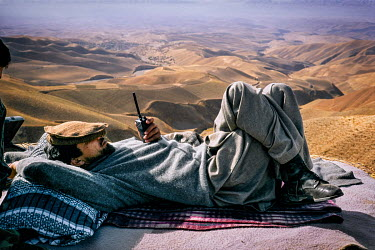 Ahmad Shah Massoud waiting for the helicopter to take him to other fronts where his forces are fighting the Taliban, rests on a vantage point above the city of Taloqan after his forces regained contro...